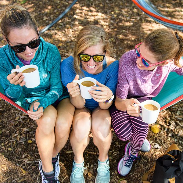 Runners hold warm drinks while sitting in a hammock