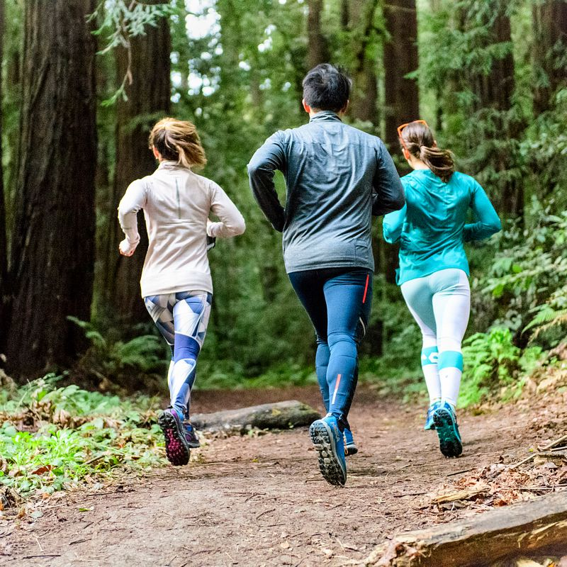 Three people run together on a trail