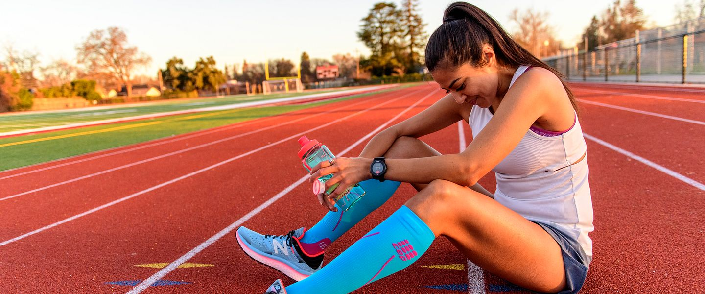 a woman sits on the side of a track to rest after a hard effort