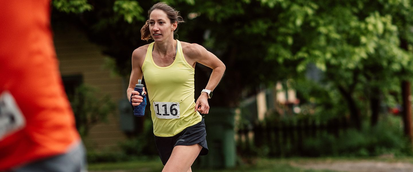 A young woman in a yellow tank runs in a 5K race