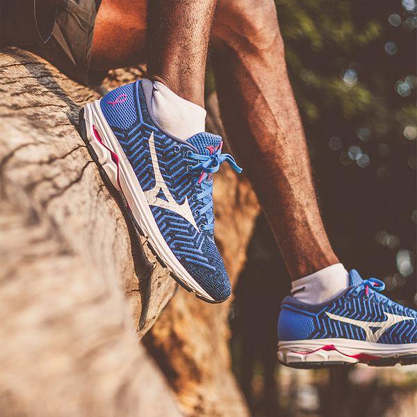 A man wearing a pair of blue Mizuno running shoes