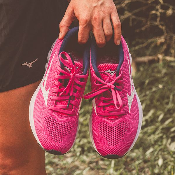 A woman holding a pair of pink Mizuno running shoes