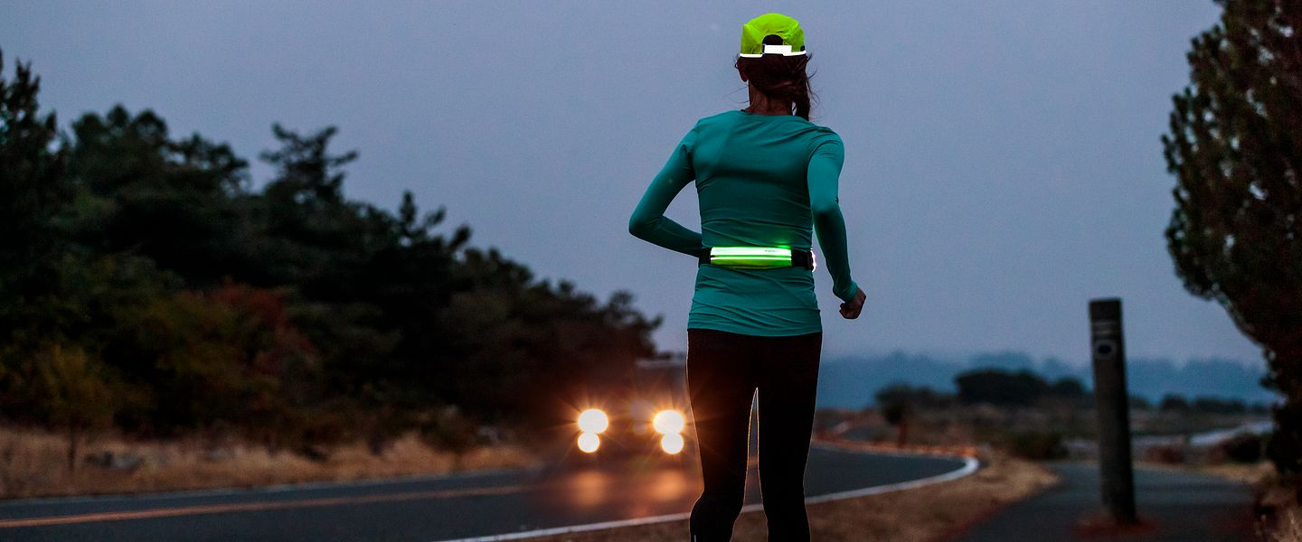 A runner wearing the Amphipod Microstretch-Flash Waistpack while running at night