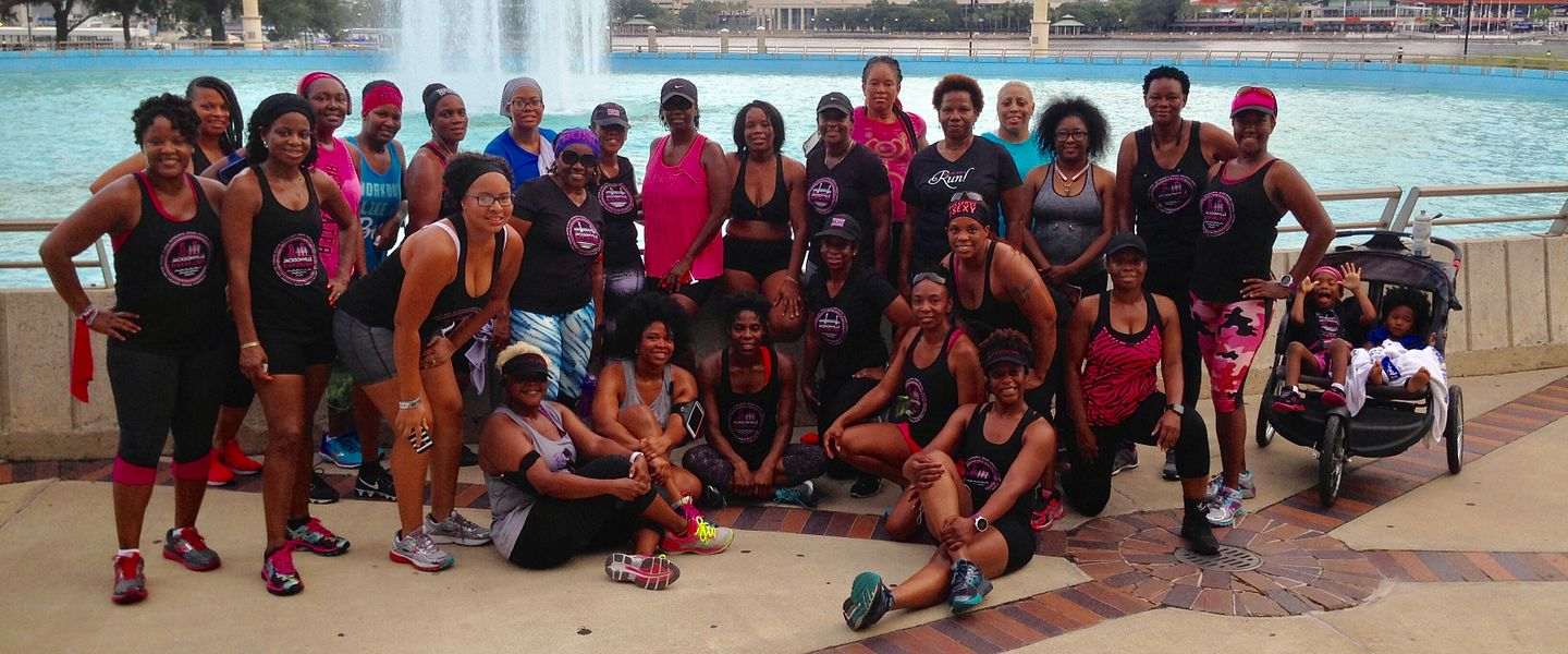 Members of Black Girls Run pose for a picture in front of a fountain.