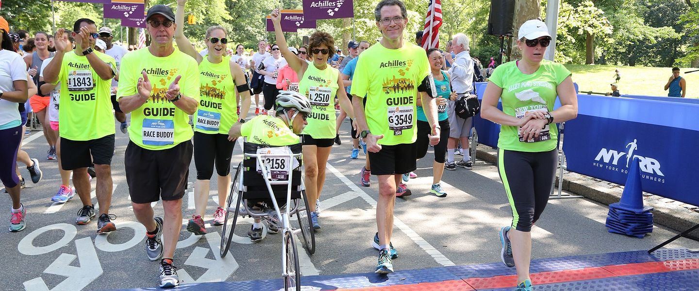 An Achilles athlete crosses a race finish line surrounded by friends and volunteers
