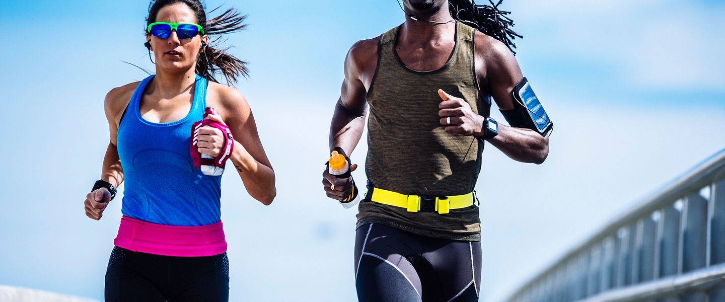 A man and woman wearing athletic clothing run together