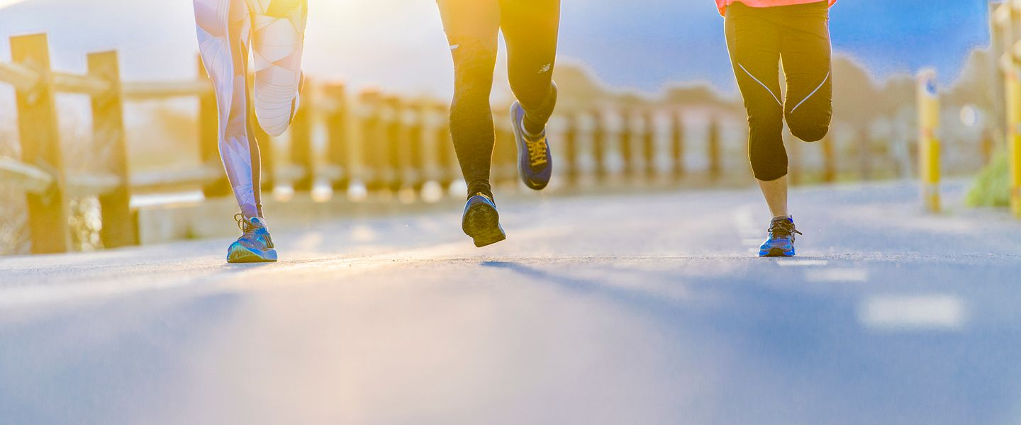Three people run together on a paved path