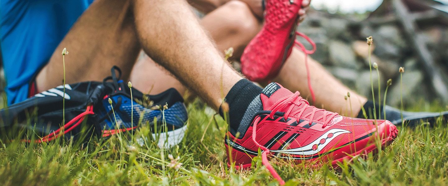 A runner changing the spikes on his Saucony cross country shoes