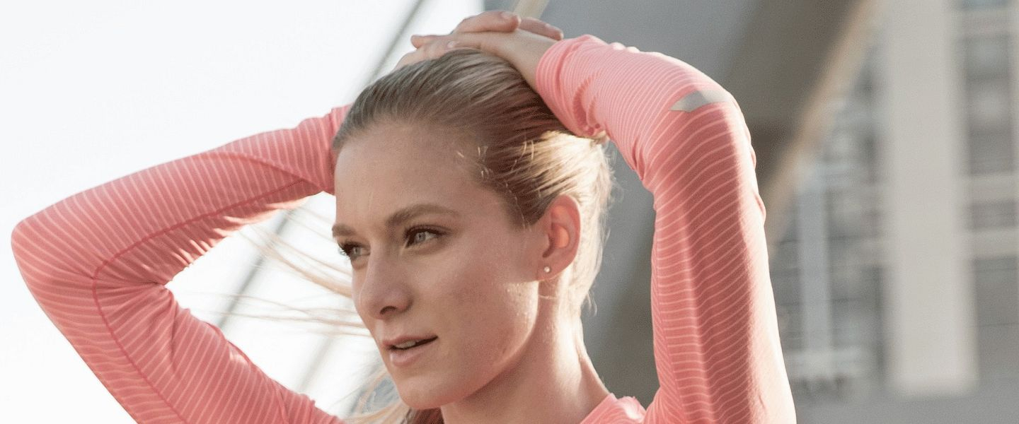 Professional runner Emma Coburn ties her hair back in a ponytail