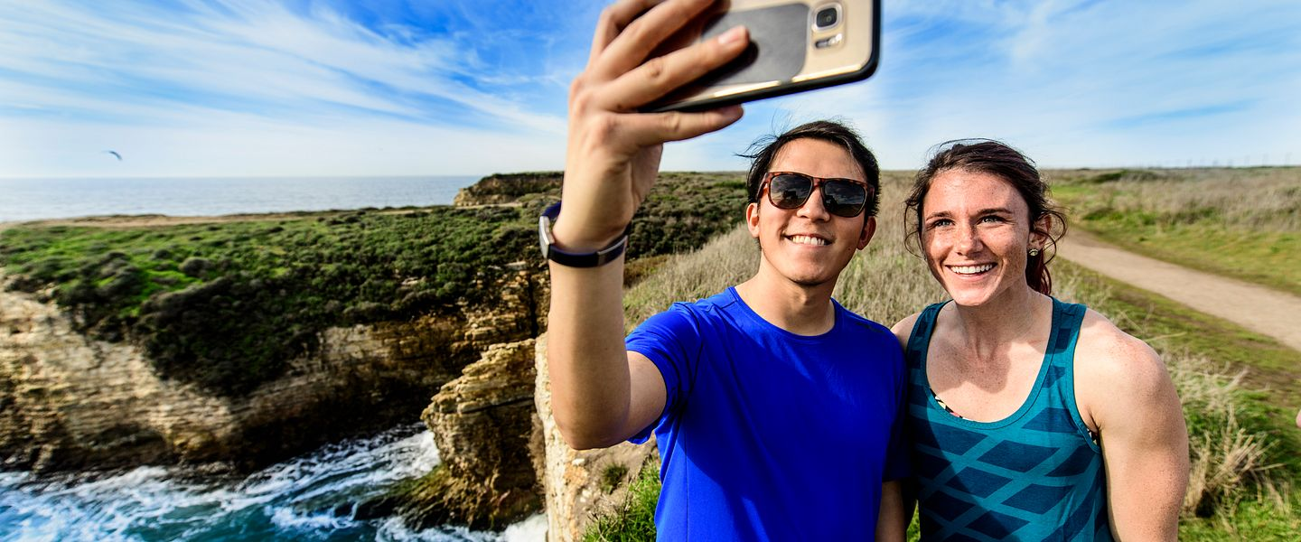 Two runners taking a selfie with a smartphone during a run