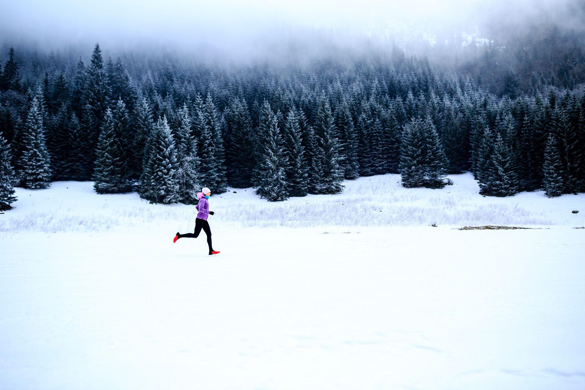 A woman wearing warm clothes runs through a snowy field