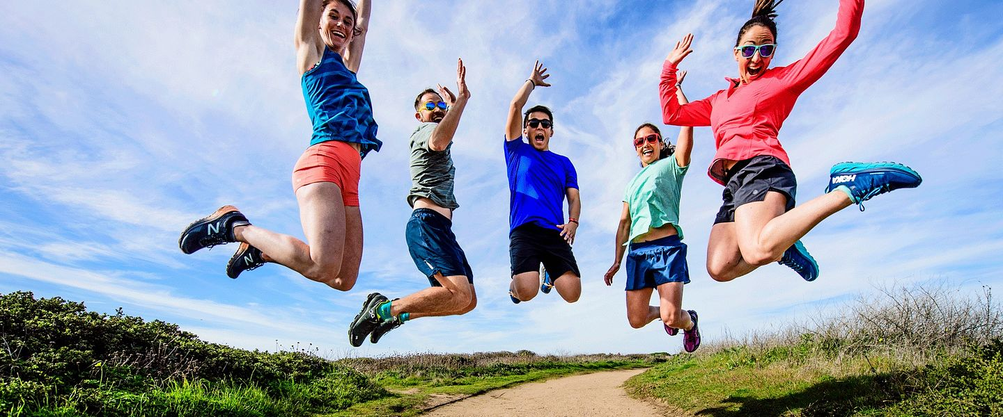 A group of runners jumps in the air together