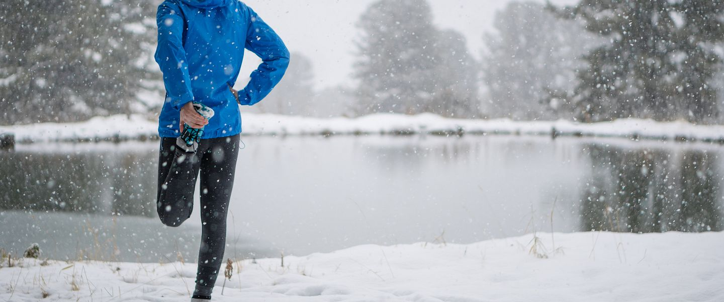 A man wearing winter running clothes stretches his leg while standing in a snowy field