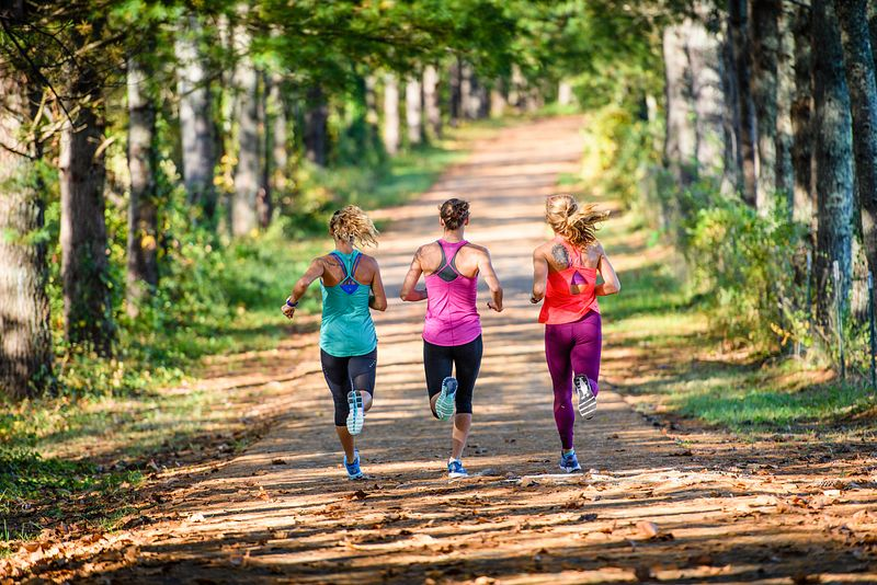 Three women running on a trail through the woods