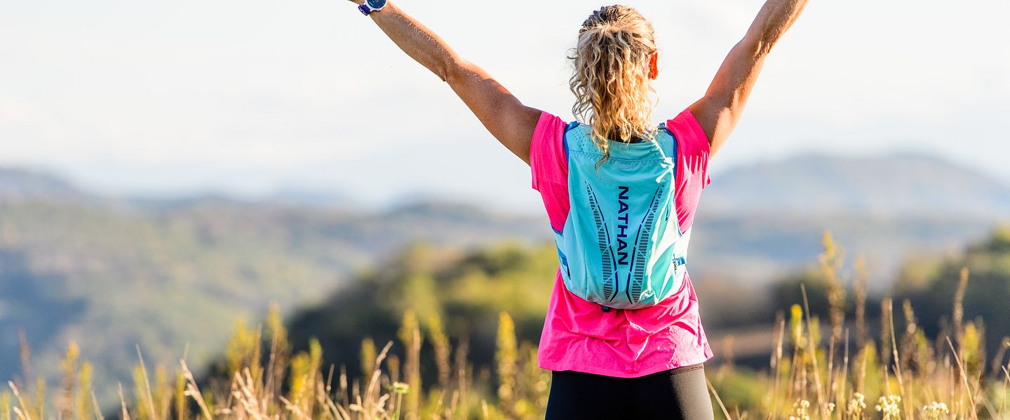 A woman wearing a hydration pack holds up her arms in celebration during a trail run