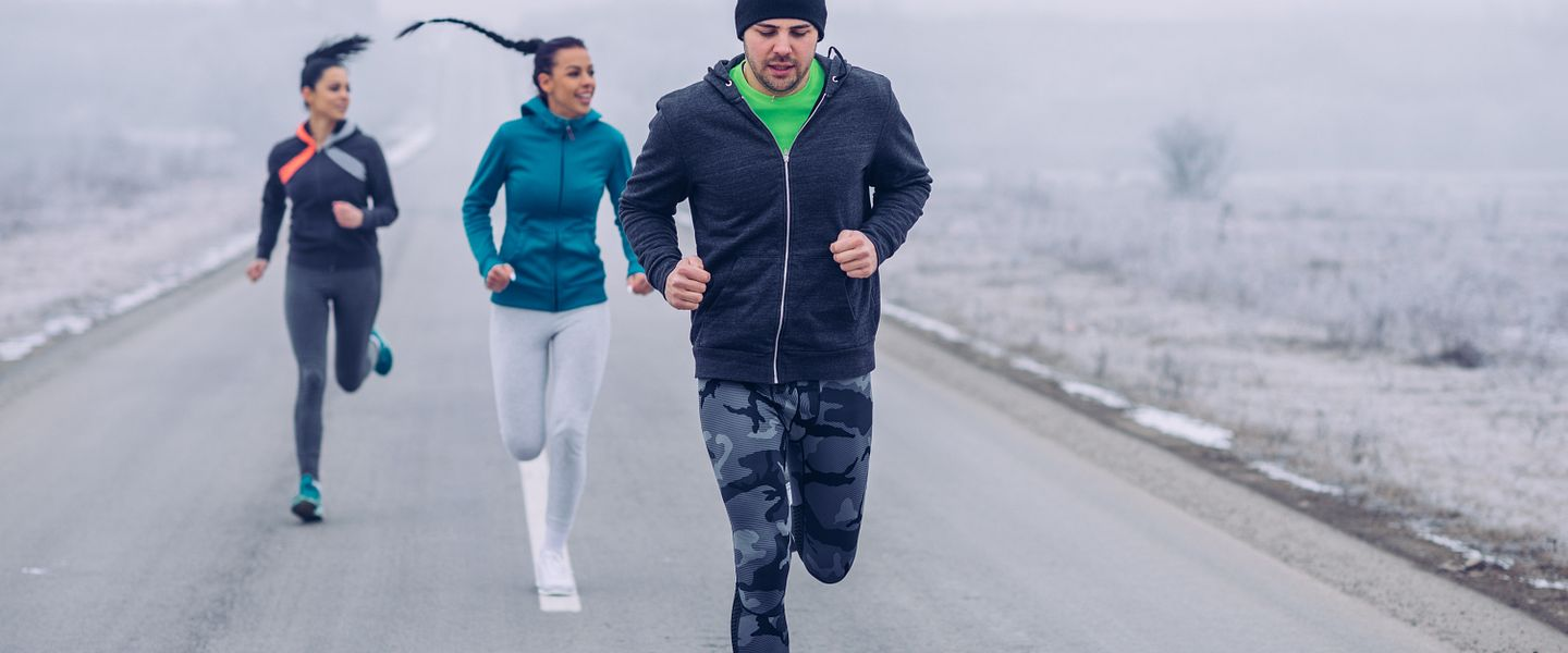 Three people wearing winter running clothes run together on a snowy street