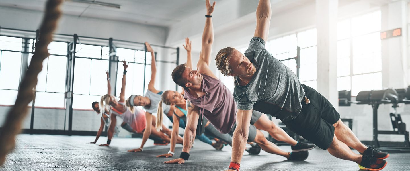 A group of people wearing athletic clothes work out together