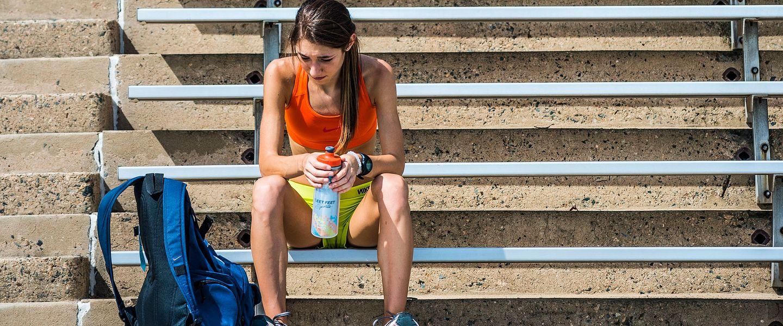 A runner in a sports bra rests on stadium bleachers after a run