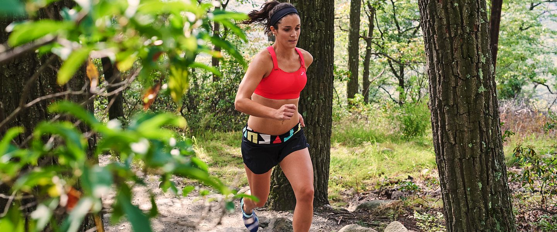 A woman wearing a Brooks Fiona sports bra runs on a trail through the woods