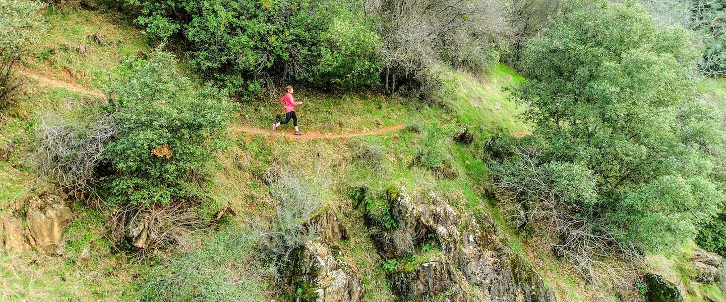 A woman runs alone on an exposed trail surrounded by greenery
