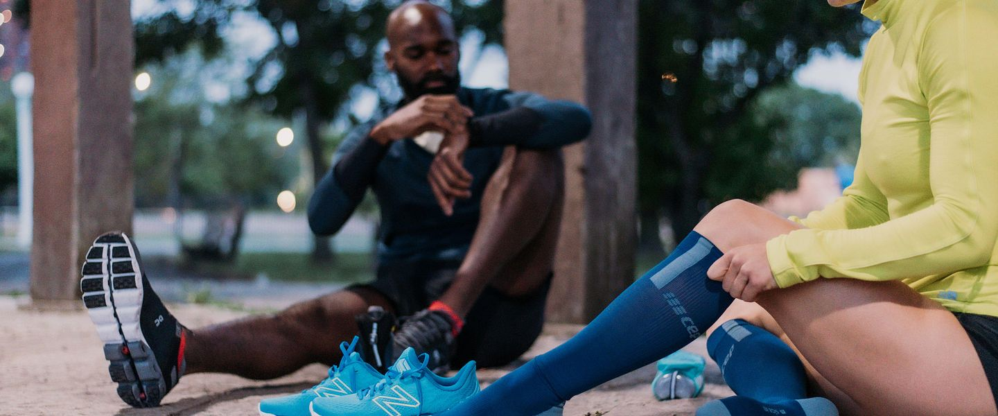 Two runners put on CEP socks before a run.