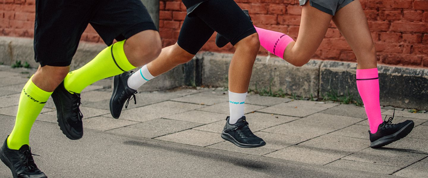 The legs of three runners wearing CEP compression socks