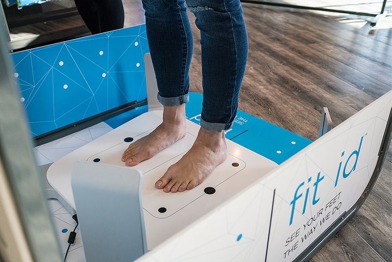 A Fleet Feet customer gets her feet scanned during a fit id process