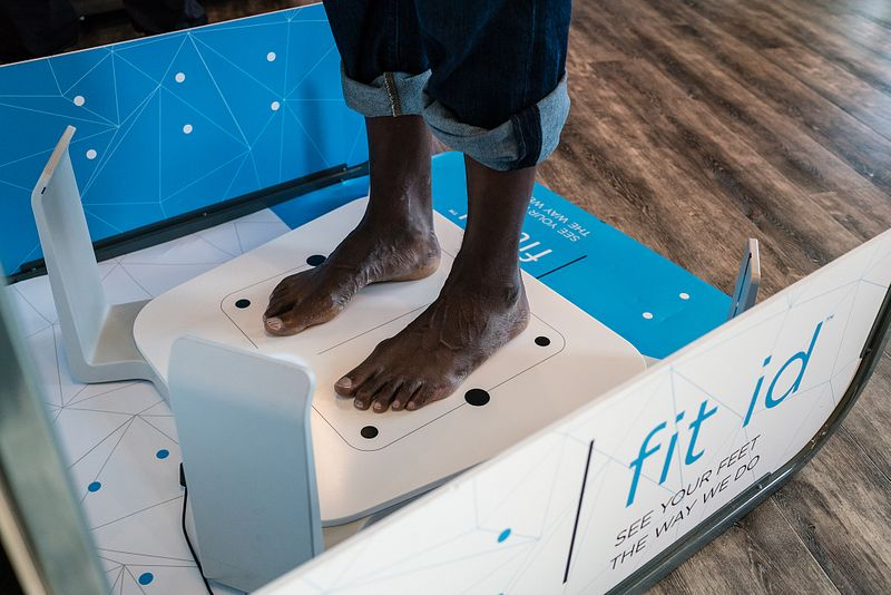 A Fleet Feet customer stands on a 3D scanner during a fit id process