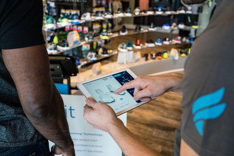 A Fleet Feet employee looks at a 3D scan of a customer's feet
