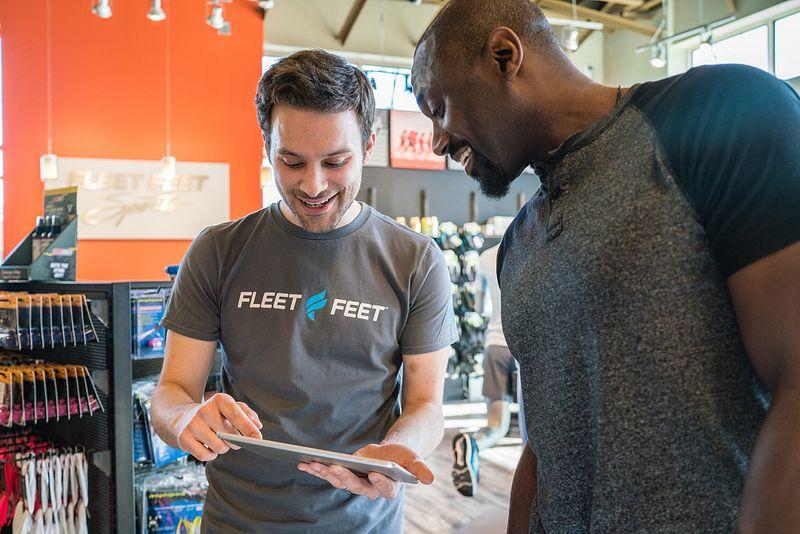 A Fleet Feet employee shows a customer a 3D scan of his feet