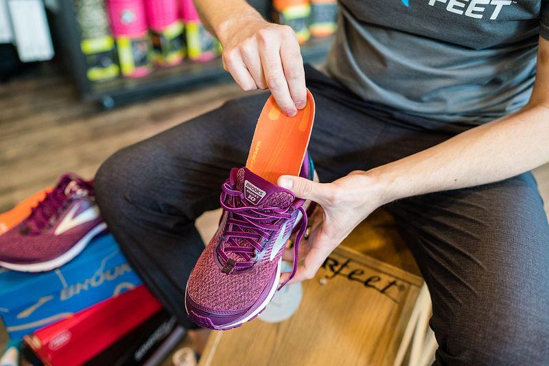 A Fleet Feet employee puts a Superfeet insole into a running shoe