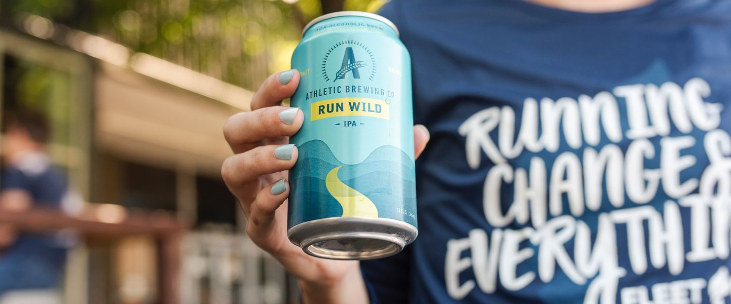 A woman holds a chilled can of Run Wild IPA by Athletic Brewing