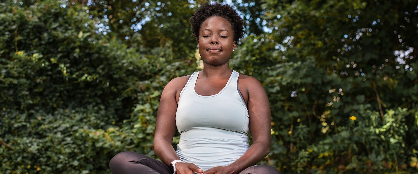 A woman meditates in a park