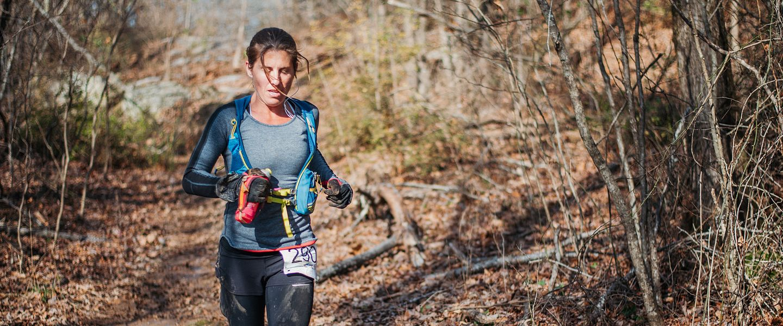 A woman runs through the woods during an ultramarathon trail race