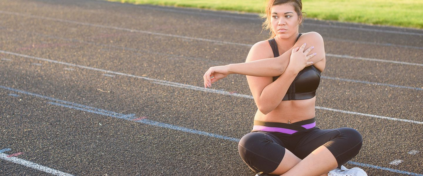 A woman wearing an Enell sports bra stretches while sitting on a track