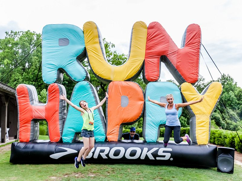 "Two women jumping in the air in front of a sign that says ""Run Happy"""