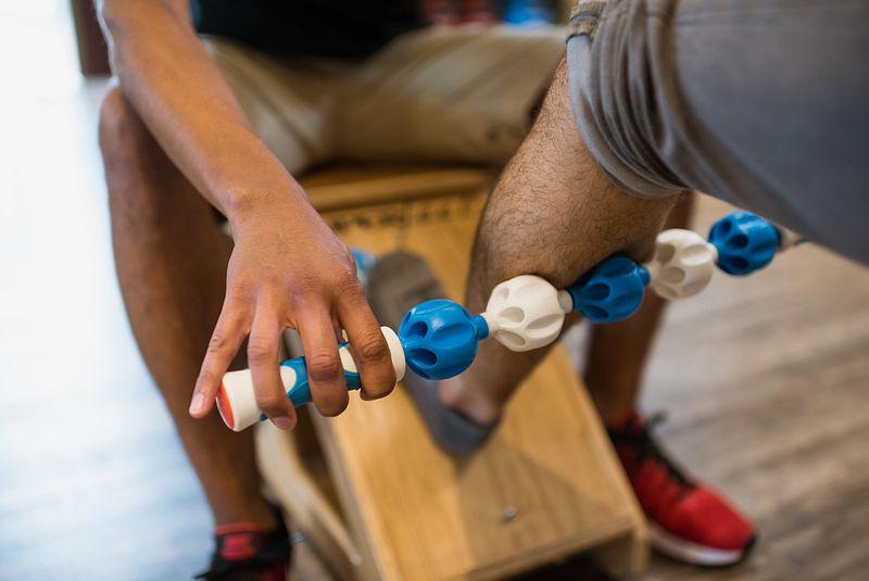 A Fleet Feet employee demonstrates how to use an addaday massage stick
