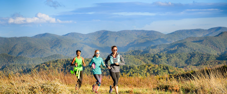 Three women run on a trail through the mountains