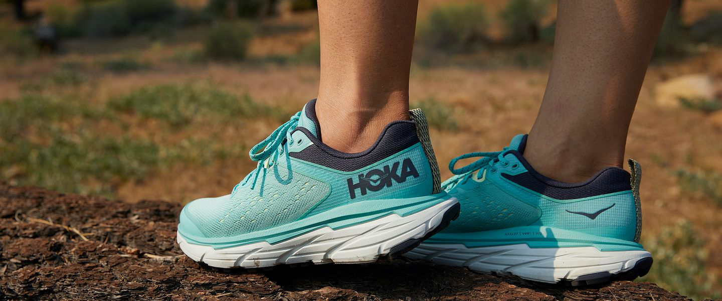 A woman wears the HOKA Challenger ATR 6 in blue