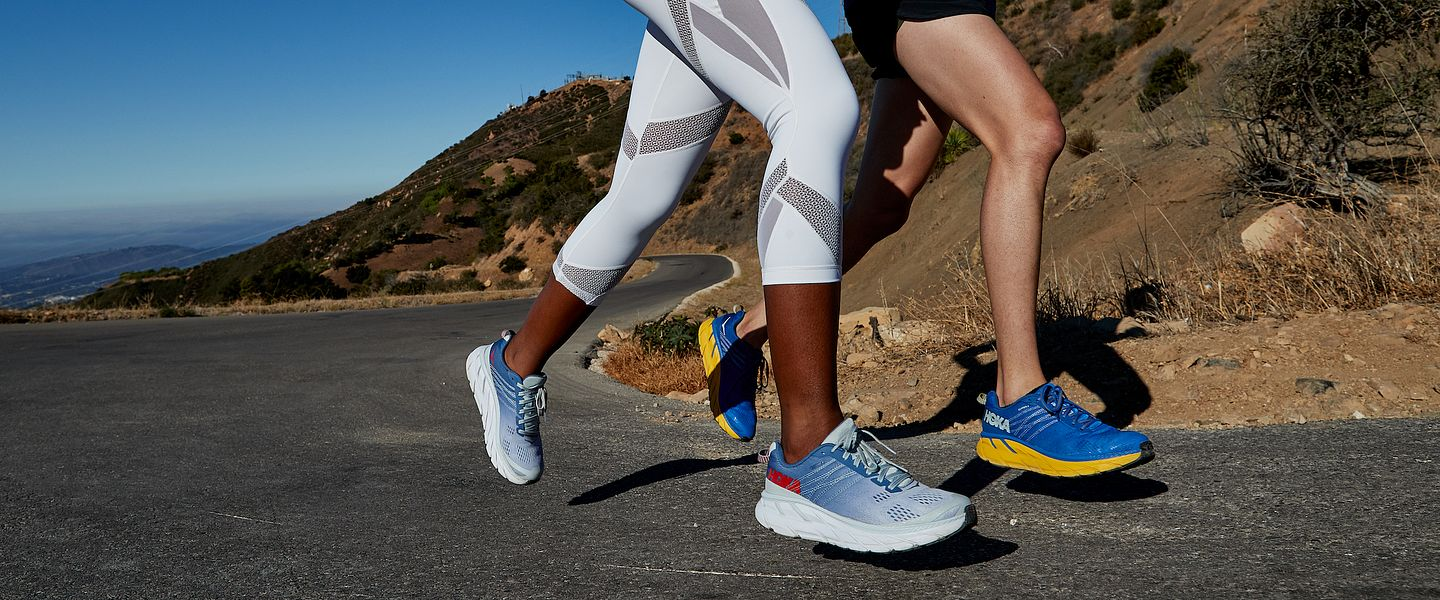 Two people run in the HOKA ONE ONE Clifton 6 shoes