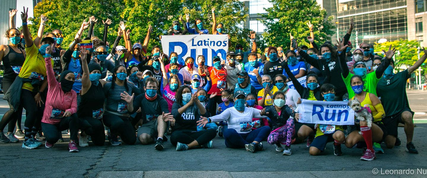 Runners from Latinos Run celebrate with banners and arms raised