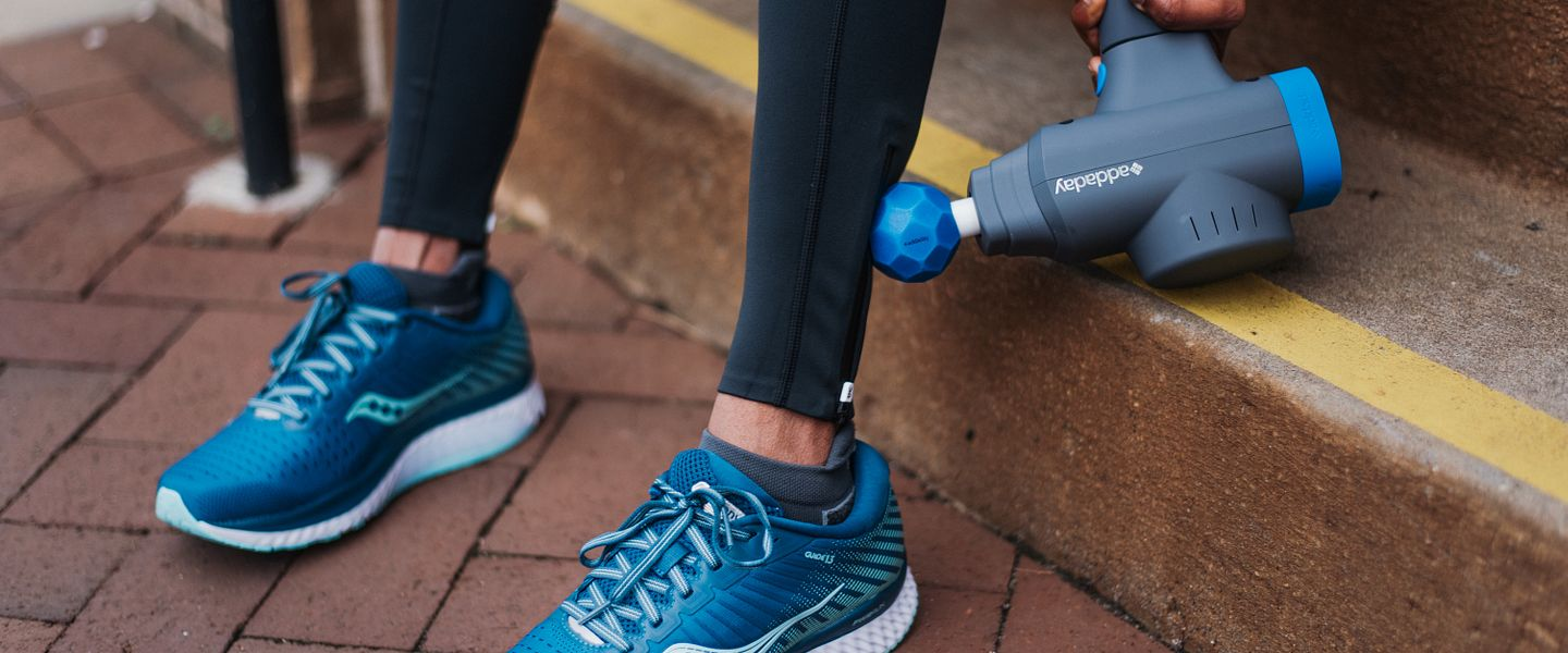 A runner using the addaday BioZoom percussion massager on her leg