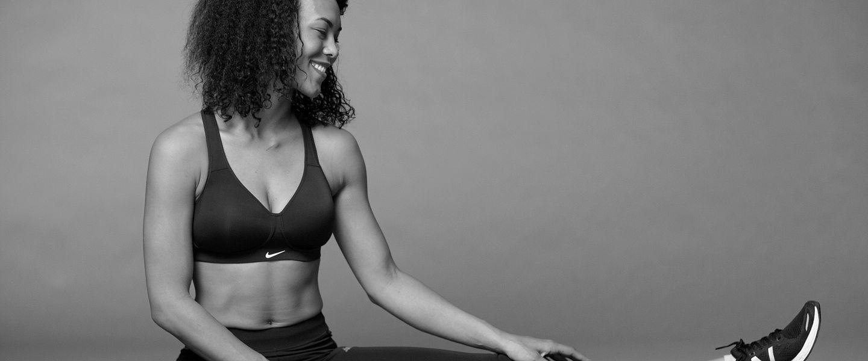 A woman wearing a Nike sports bra stretches her leg