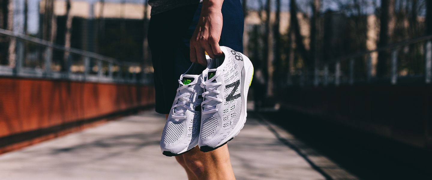 A runner holds a pair of the New Balance 890v7