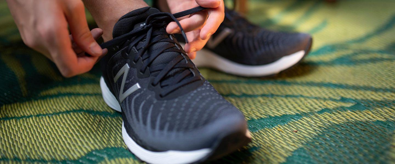 A runner tying a pair of New Balance Fresh Foam 860v11 running shoes