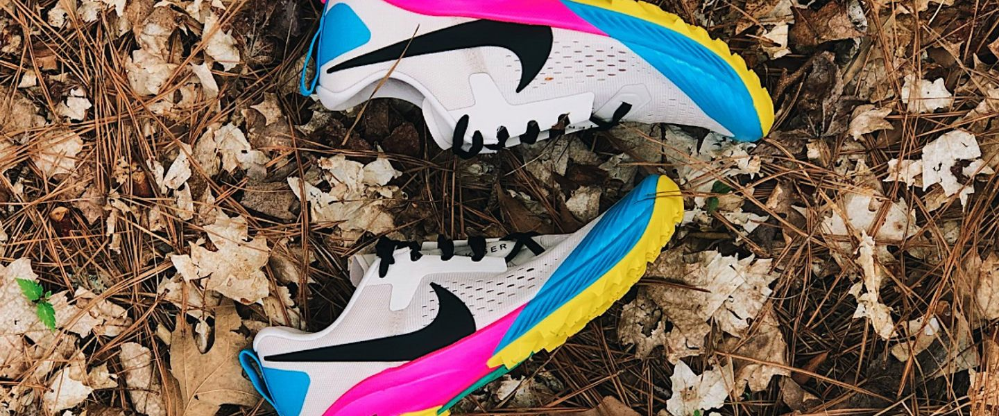 A pair of Nike Terra Kiger 5 trail running shoes on a leafy trail