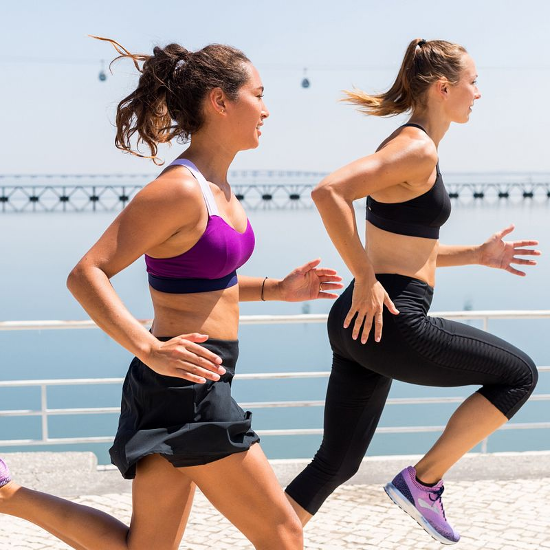 Two women wearing Brooks sports bras run together