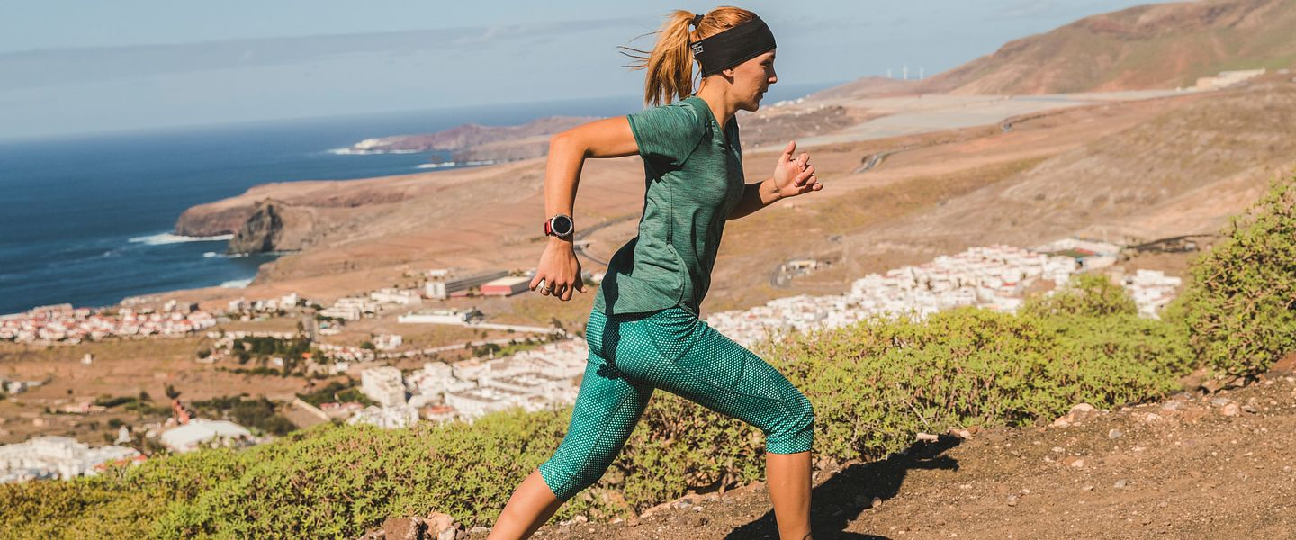 A woman runs in the Saucony Switchback ISO trail running shoe