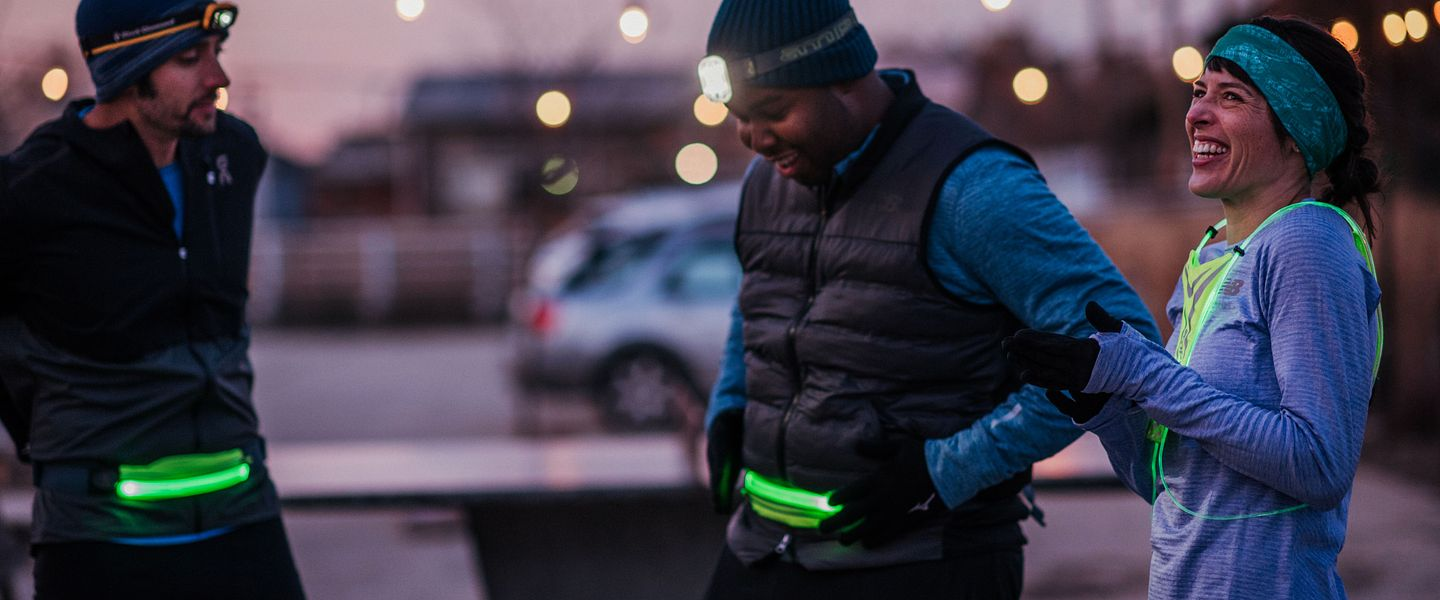 Three people wearing warm running clothes and lights get ready for a run