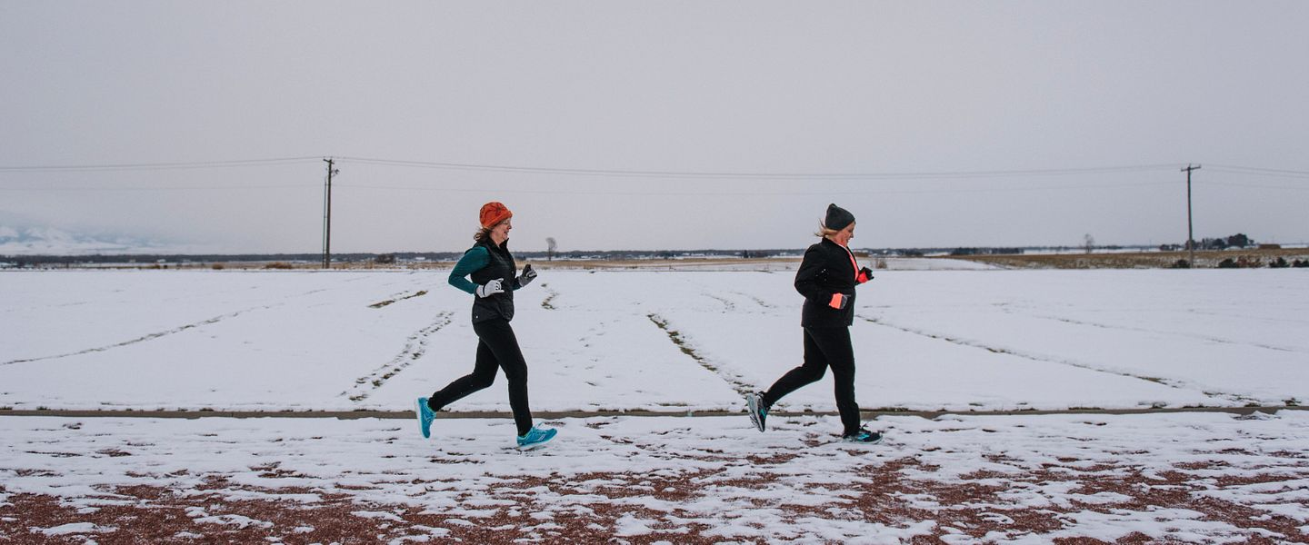 Two women run together during the winter on a snow-covered track
